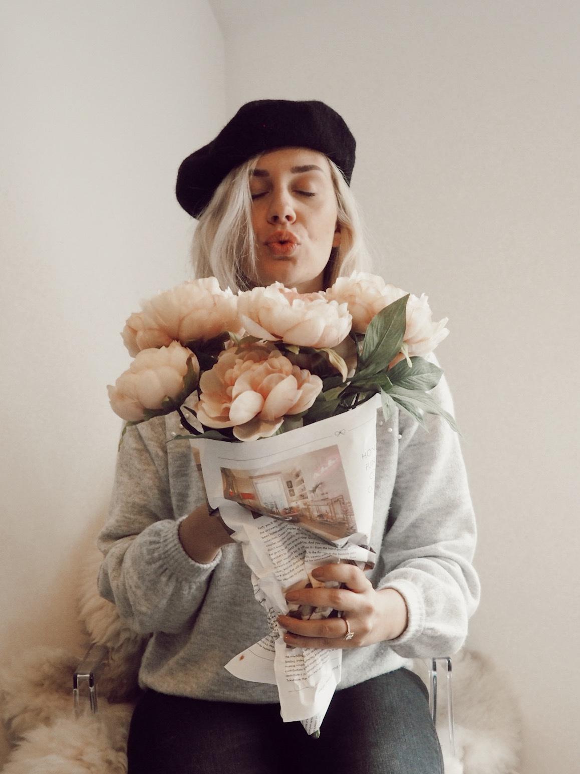 girl in beret holding flowers