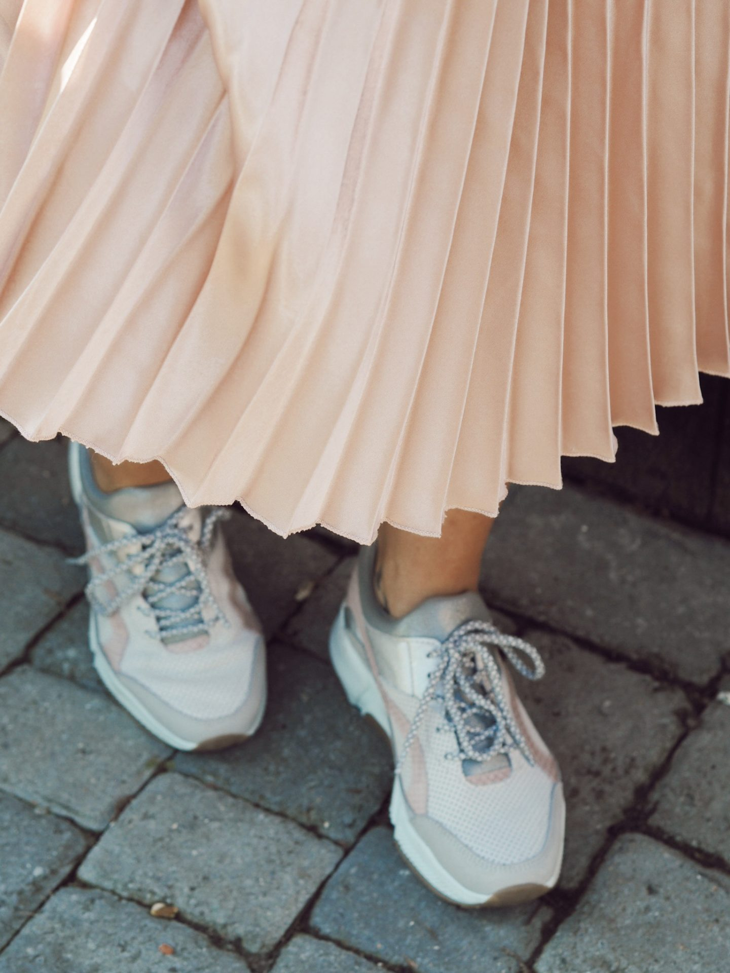 girl in pink skirt and moda in pelle trainers
