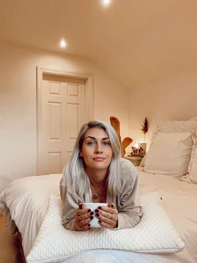 blonde_girl_laying_on_bed_with_tempur_pillow_and_a_cup_of_tea